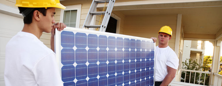 Contractors installing solar panels at house