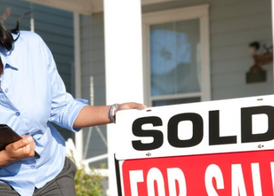Person in front of home with for sale sign